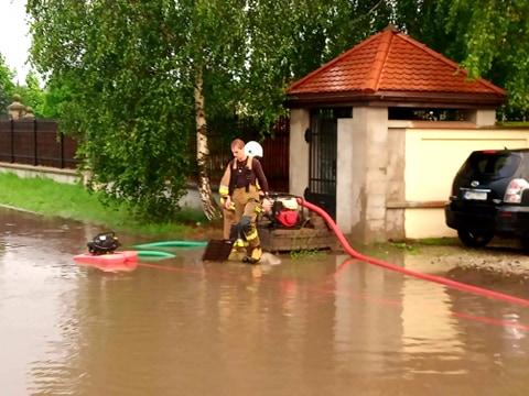 strażacy wypompowują wodę z drogi