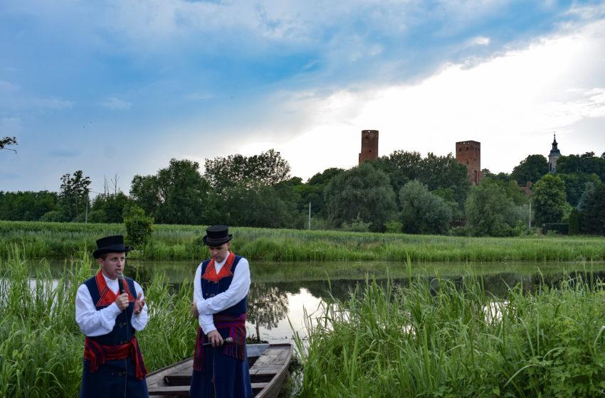 Urzecze - panowie w stroju ludowym na tle zamku w Czersku