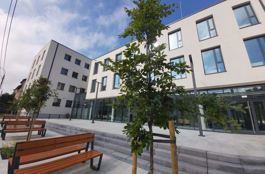 Nowy budynek urzędu pracy, drzewa i ławki pod wejściem